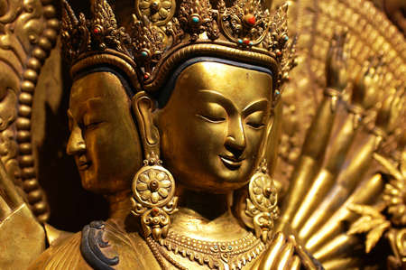 Ancient golden sculpture of a buddha with four faces and eight hands photo