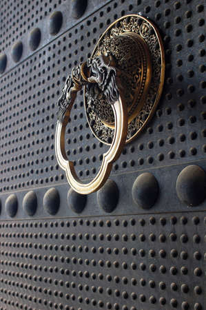 Ancient iron door with a copper doorknob photo