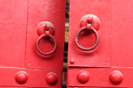 Closeup view of red doors with iron doorknobs photo