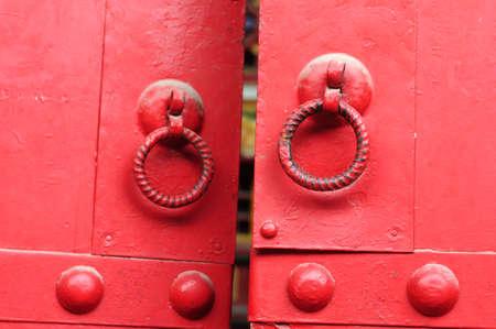 Closeup view of red doors with iron doorknobs photo