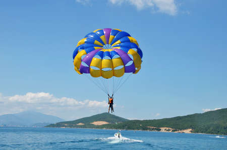 Landscape of paragliding on beach with blue skies and mountains as backgrounds photo