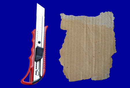 Paper knife and old cardboard isolated on a blue background photo