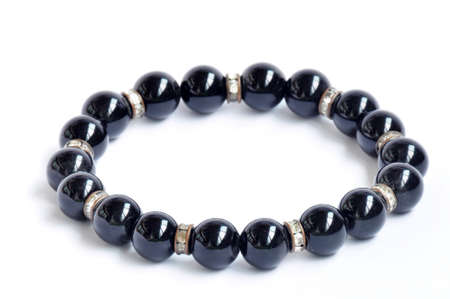 Bracelet made of black pearls on a white background