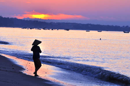 Silhouette of a fisherman on beach at sunrise Stock Photo