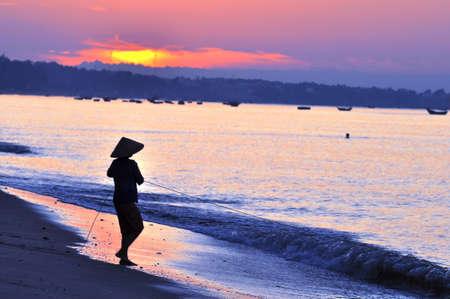 vietnam: Silhouette of a fisherman on beach at sunrise Stock Photo