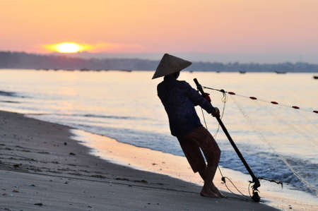 Silhouette of a fisherman on beach at sunrise photo