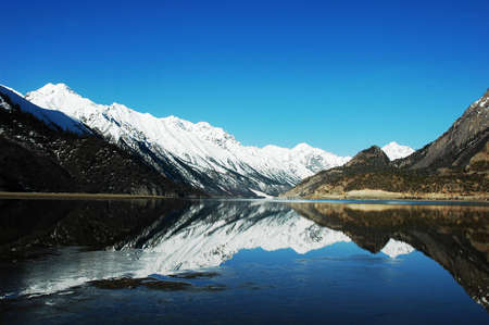 Landscape of snow-capped mountains with a mirror in the lake photo
