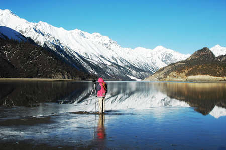 Landscape of snow-capped mountains with a photographer taking photos in the lake