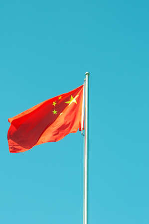 Chinese national five-star red flag fluttering in the wind against blue sky photo