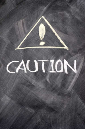 Caution written on blackboard with exclamation mark photo