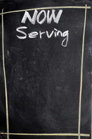 Menu of now serving written with chalk on a blackboard photo