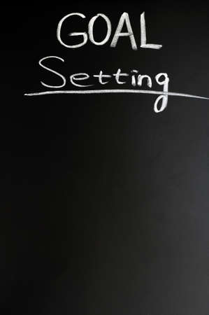 attainable: Goal setting written with chalk on a blackboard