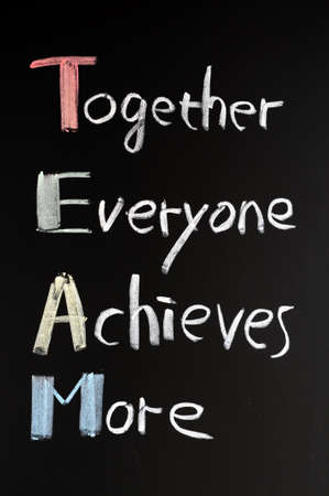achieves: TEAM acronym (Together Everyone Achieves More), teamwork motivation concept of chalk handwriting on a blackboard