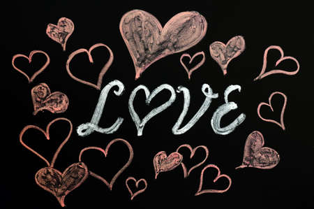 Love with heart shapes drawn with chalk on a blackboard photo