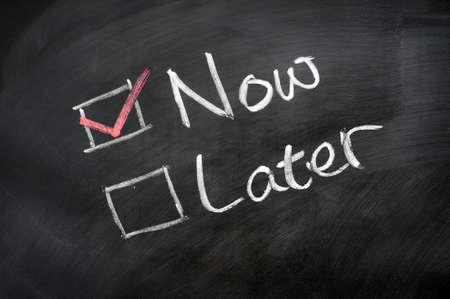 Nu en Later selectievakjes geschreven op een schoolbord Stockfoto