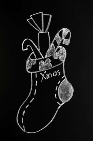Christmas sock with presents drawn with white chalk on a blackboard photo