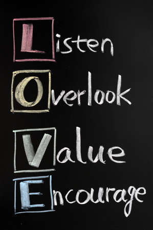 encourage: LOVE acronym, listen, overlook, value, encourage on colorful sticky notes on a blackboard with words written in chalk.  Stock Photo