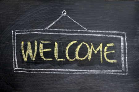 welcome door: Benvenuti - parola scritta con il gesso giallo su una lavagna