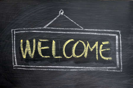 welcome sign: Welcome - word written with yellow chalk on a blackboard Stock Photo