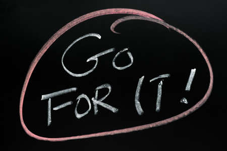 Red circle around the phrase Go For It!on a blackboard  Stock Photo