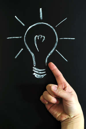 Light bulb drawn with chalk on blackboard, with a finger pointing to it photo