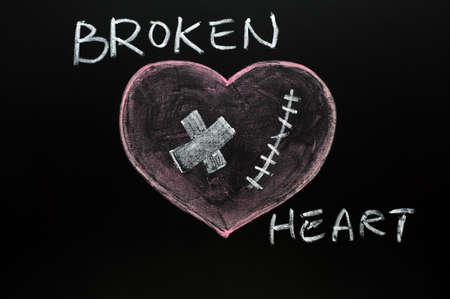 wounded heart: Broken heart drawn with chalk on a blackboard