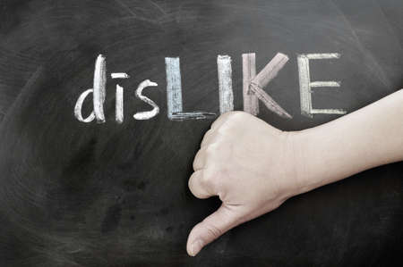 Thumb down with dislike on a blackboard photo