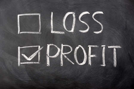 Loss and profit check boxes on a blackboard with profit checked photo