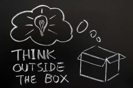 Think outside the box drawn in chalk on a blackboard photo