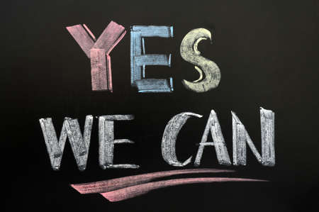 Yes we can - text written in colorful chalk on blackboard photo
