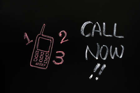 Call now symbol of a cellphone on blackboard photo