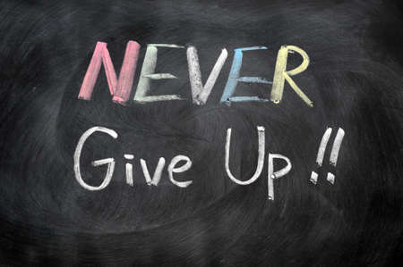 never: Never give up written in chalk on a blackboard Stock Photo