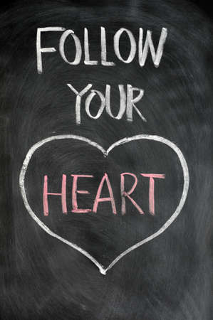 follow: Follow your heart drawn in chalk on a blackboard Stock Photo