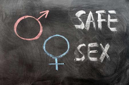 educacion sexual: Concepto de sexo seguro con símbolos de género escritas en una pizarra