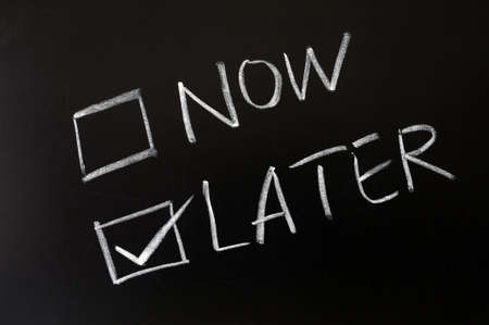 later: Now and later check boxes with later chosen on a blackboard Stock Photo