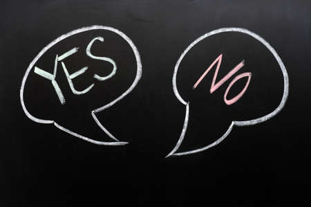 yes or no: Two speech bubbles with yes and no on a blackboard Stock Photo