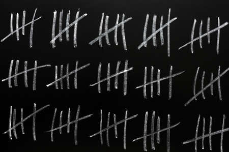 tally: Counting by tally chart drawn in chalk on a blackboard Stock Photo