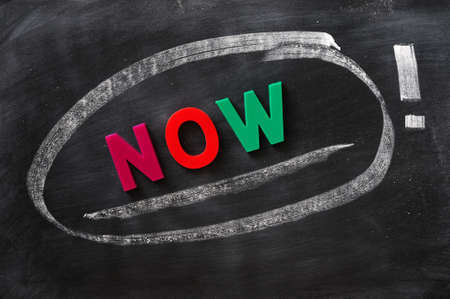 Now - word made of colorful letters on a smudged blackboard Stock Photo - 11939588