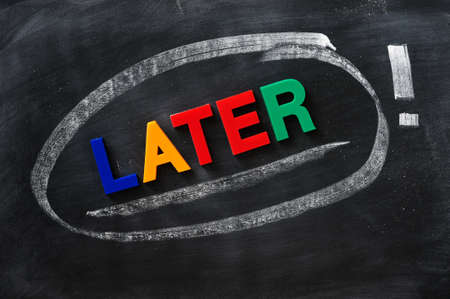 later: Later - word made of colorful letters on a smudged blackboard