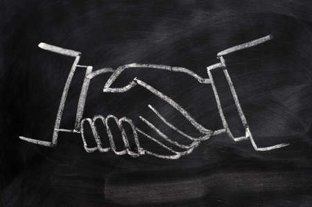 Handshaking sign drawn in chalk on a smudged blackboard