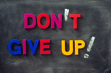 never: Dont give up - text made of colorful letters on a smudged blackboard