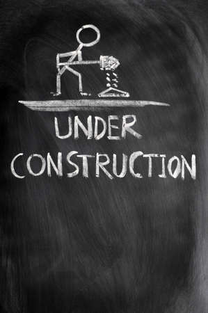 Under construction concept drawn in chalk on a blackboard photo