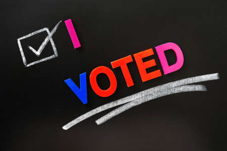 i voted: I voted - text made of colorful letters on a blackboard Stock Photo