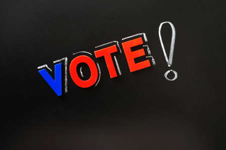 Vote with a big exclamation mark on a blackboard photo
