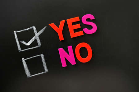 yes no: Yes or no check boxes with yes checked on a blackboard Stock Photo