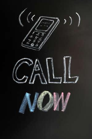 Call now - text written in chalk on a blackboard photo