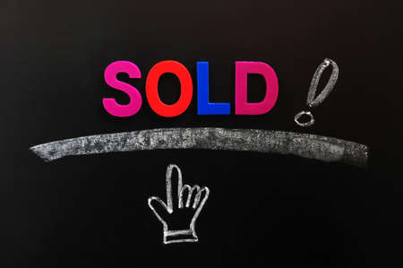 Sold - word with an exclamation mark and hand cursor on a blackboard photo