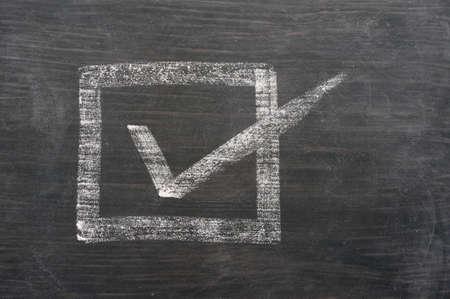 voting box: Casella di controllo con una crocetta disegnata con il gesso su una lavagna