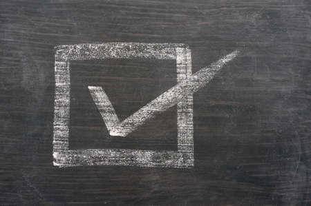 blank check: Check box with a tick drawn in chalk on a blackboard