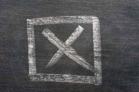 Check box with a cross drawn in chalk on a blackboard photo